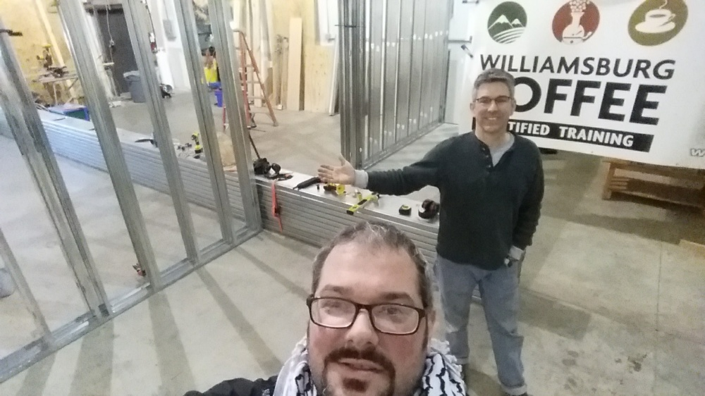 Two men stand taking a selfie in a construction zone with a wall being built in the background and sign for Williamsburg Coffee Certified Training