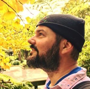 Thomas smiles in profile before brilliant yellow ginko trees.
